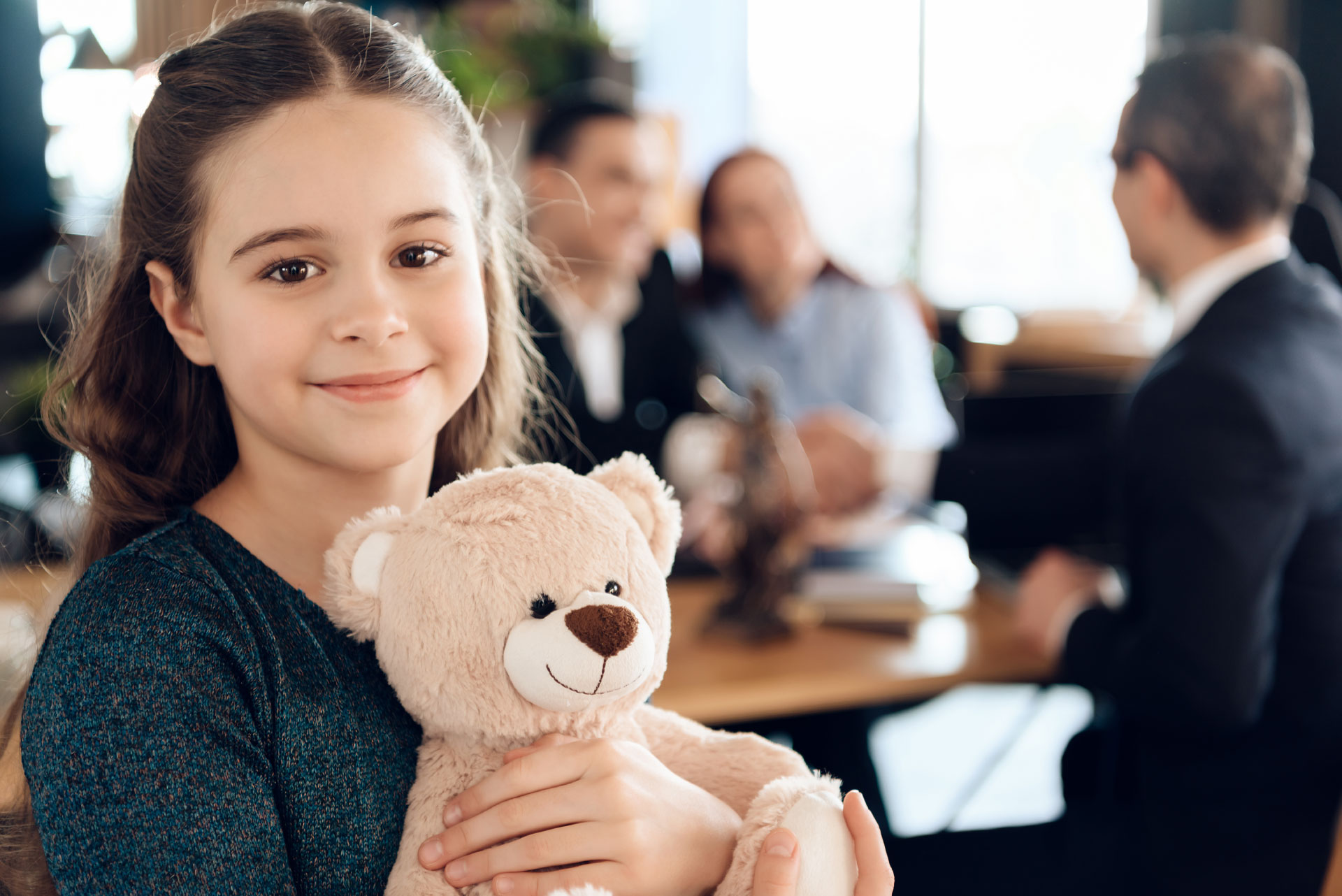 Image of a child holding a stuffed teddy bear